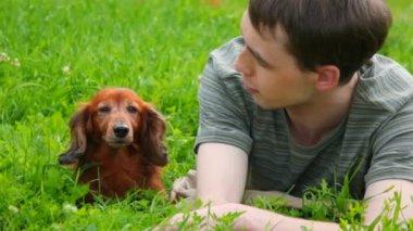 Homem deitado na grama verde, falando com o cachorro — Vídeo Stock
