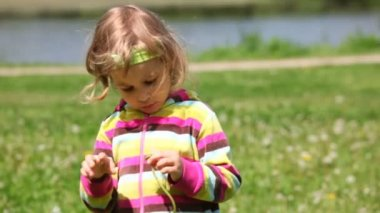 Girl in the purple blouse plays with dandelion — Stock Video