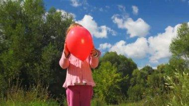 Petite fille vomir ballon rouge dans le parc — Vidéo