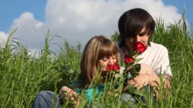 Young man and girl smelling flowers and kissing each other — Stock Video