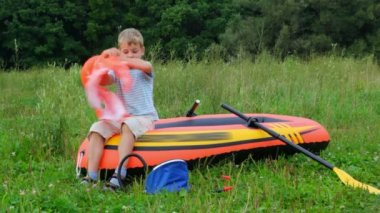 Boy puts on a life jacket sitting on an inflatable rubber dinghy — Stock Video