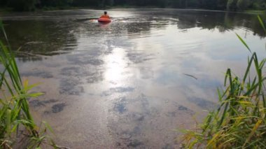 Homem com menino, remar um barco inflável da costa — Vídeo stock