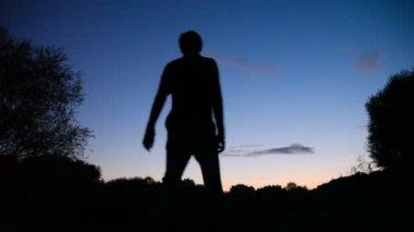 Man turning round on sunset background — Stock Video