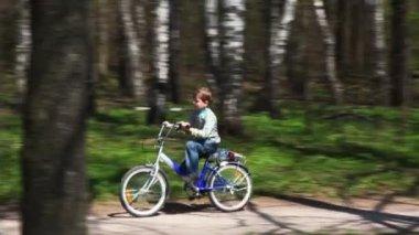 Niño va en bicicleta en un camino forestal en primavera — Vídeo de Stock