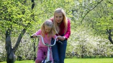 Mãe ensina a menina a rolar em bicicleta — Vídeo Stock