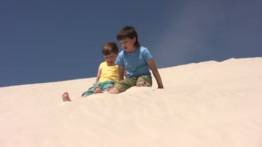 Kids scramble down by the sand — Stock Video