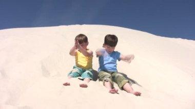 Chicos derraman la arena en las piernas — Vídeo de Stock