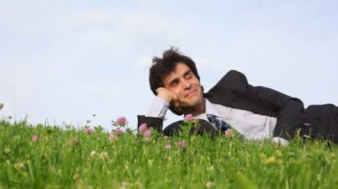 Szczęśliwy przystojny mężczyzna leży na zielonej trawie i nogi przechodzień — Wideo stockowe