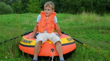 Boy dressed in life jacket dragging inflatable rubber — Stock Video