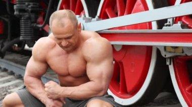 Bar överkropp bodybuilder plats på järnvägen mot lokomotiv — Stockvideo