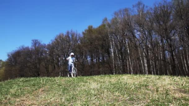 Niño va en bicicleta por el campo en primavera — Vídeo de stock