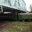Commuter train passes quickly under iron bridge in autumn — Vídeo Stock
