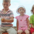 Stock Video: Two little girls sits with boy dividing orange, blue sky in background