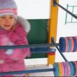 Little girl playing with abacus in winter city playground - Stockfoto