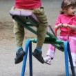 Boy and girl play at seesaw together on playground - Foto Stock