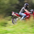 Motorcyclists on red bike crosses field in park — Stock Video