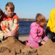 Stock Video: Family of mon, dad, son and daughter build hills of sand together on river beach