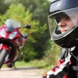 Biker sit down on motorcycle and close visor on it helmet — Stock Video