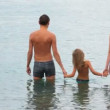 Family of three persons standing in sea and squating, join hands - Foto de Stock