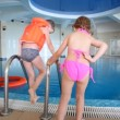 Boy and little girl get ready to swimming in indoor pool - Foto Stock