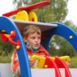 Young boy swinging in toy helicopter in children playground - Stockfoto