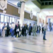 Queueing up in ticket office, camera moving across, blurred - Stock Photo