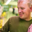 Stock Video: Smiling man with little girl buying parsley in supermarket
