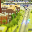 In small model city train goes from station on rail near to factory and church — Stock Video
