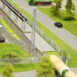 Train pushes tank wagon on rail in modern toy city to fuel station among roads with small cars and trees - Stock Photo