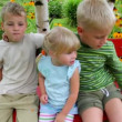 Four kids seating on the bench in the yard — Stock Video #18191553