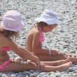 Two little girls sitting on stones and putting stones on their legs, side view — Stock Video