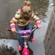 Talking little girl sits on bicycle on wet asphalt with puddles - Stock Photo