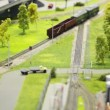 Train pushes freight cars on rail in modern toy city among roads and trees — Stock Video