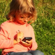 Girl sit in park, hold communicator in hands and play in it — Stock Video