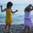 Two little girls dancing in evening pebble beach, sea in background — Stock Video #18191975