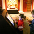 Boy and girl looks at interactive display in museum - Stockfoto