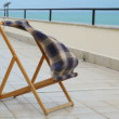 Chair standing in verandah of hotel with sea view, material waving by wind - Stock Photo