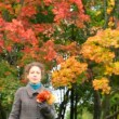 Young woman with autumn red leaves in hand walking to camera in park — Stock Video