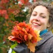 Portrait of smiling young woman with autumn leaves in park — Stock Video