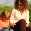 Daughter with mother play in communicator in park in summer — Stock Video