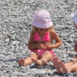 Two little girls sits on stones and puts stones on their legs, front view — Stok video