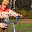 Boy with bicycle standing against forest - Stock Photo