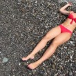 Woman dressed in swimsuit lying on pebble beach with sea surf — Stock Video