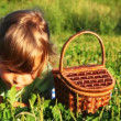 Little girl lies in grass near backet, eats cherry and smile — Stock Video #18193159