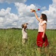 Mother and son playing with airplane in the filed - Stock Photo