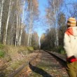 Boy walking along railroad tracks, from camera — Stock Video