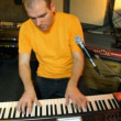 Yellow T-shirted keyboard player playing on synthesizer in studio — Stock Video #18193841