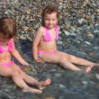 Two laughing little girls sitting on pebble beach with sea surf — Stock Video