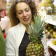 Stock Video: Smiling man and woman buying pineapple in supermarket