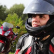 Motorcyclists sits near motorcycle, see and turn head — Stock Video